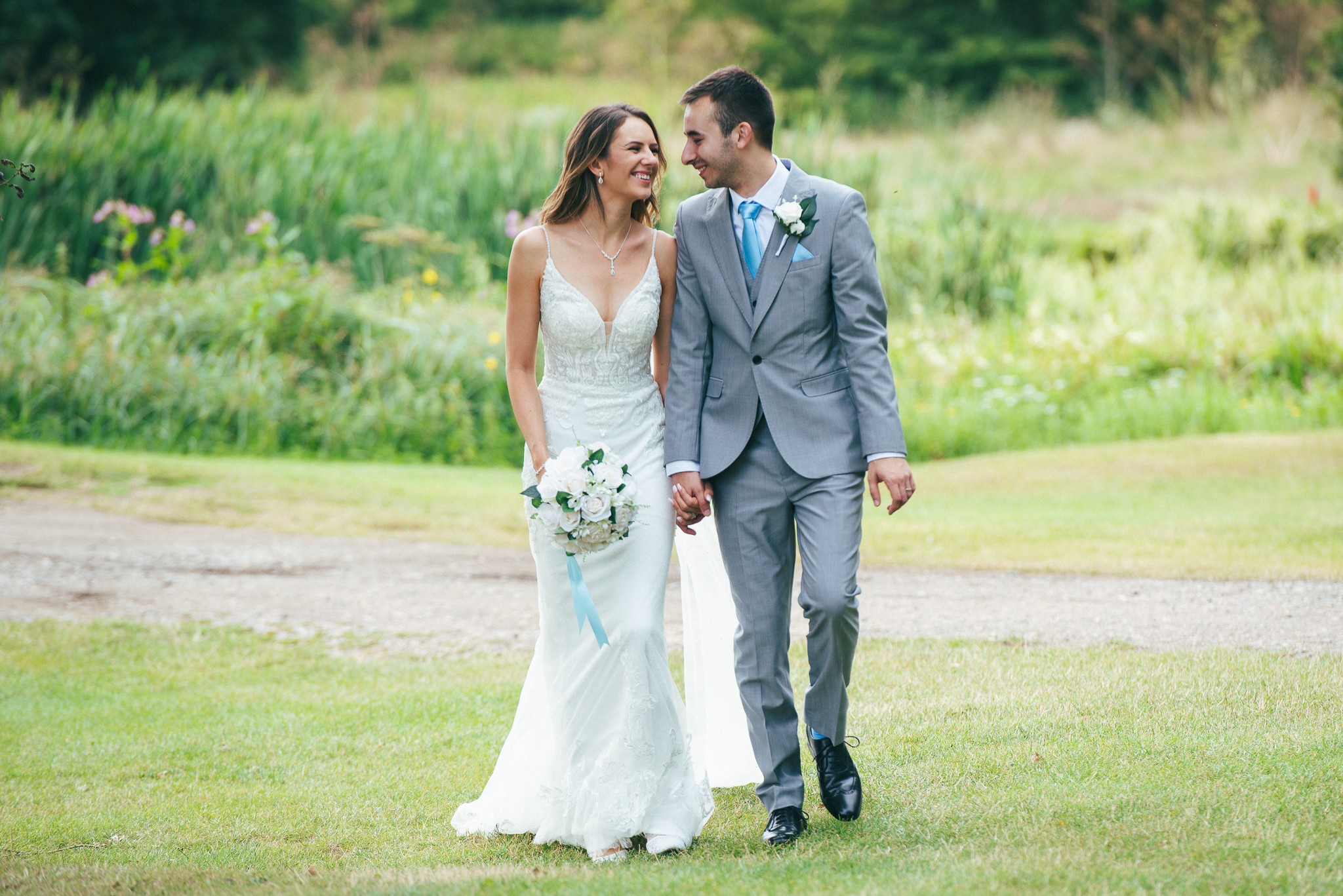 Wedding couple walking towards the camera on grass and looking at each other