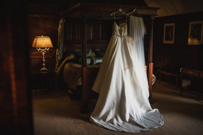 Wedding dress hung on a four post bed in a wood panel room